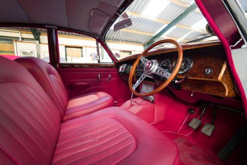 Photograph of the interior of a classic Jaguar, with red leather seats and trim.
